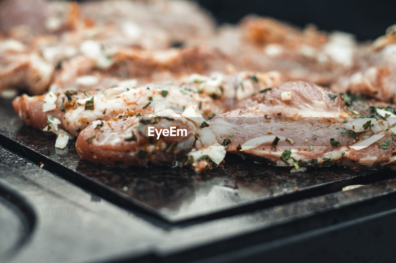 grilling pork neck meat on a granite stone laid on heat of fire. meat sprinkled with salt, basil
