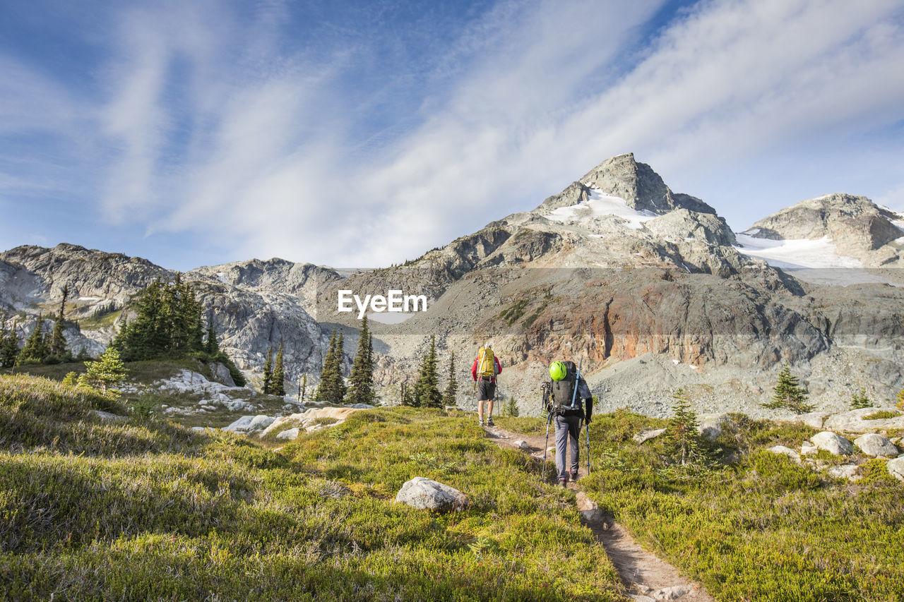REAR VIEW OF PEOPLE WALKING ON MOUNTAIN