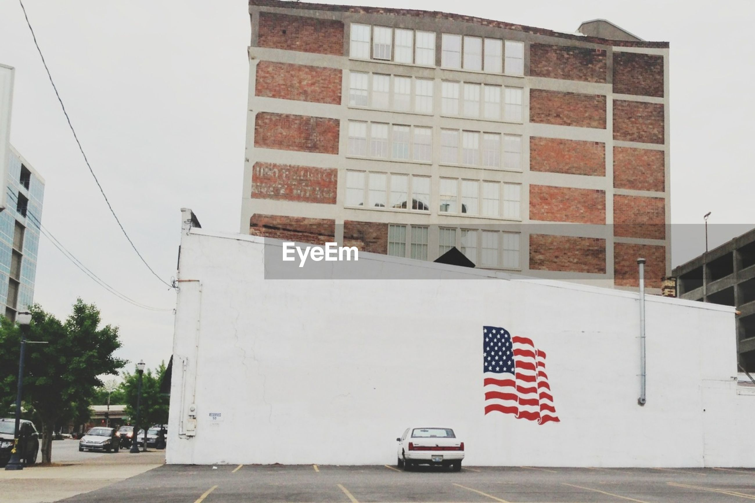 Lone car parked against american flag on wall