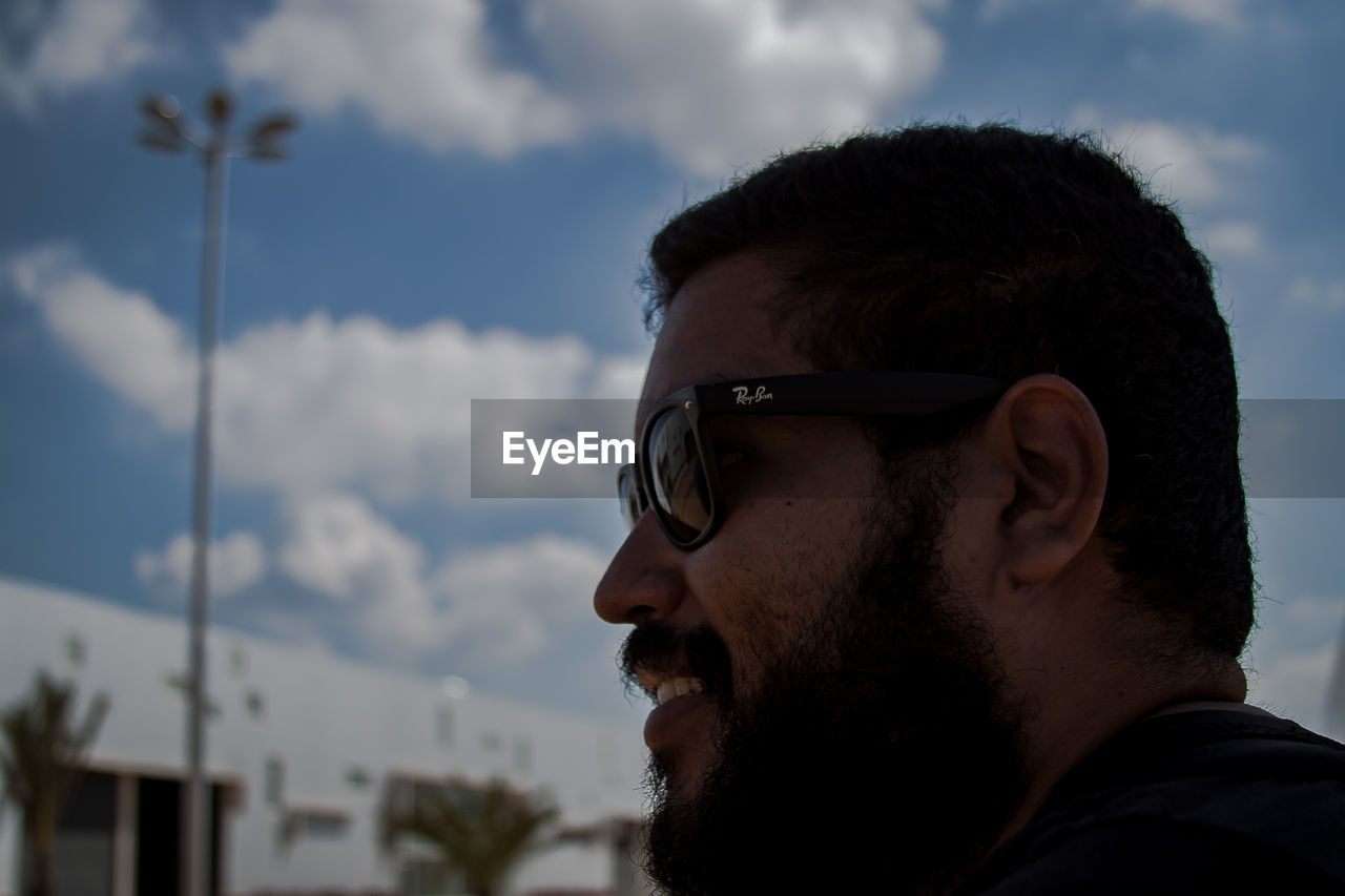 sunglasses, sky, real people, one person, cloud - sky, young adult, young men, lifestyles, leisure activity, headshot, outdoors, focus on foreground, low angle view, day