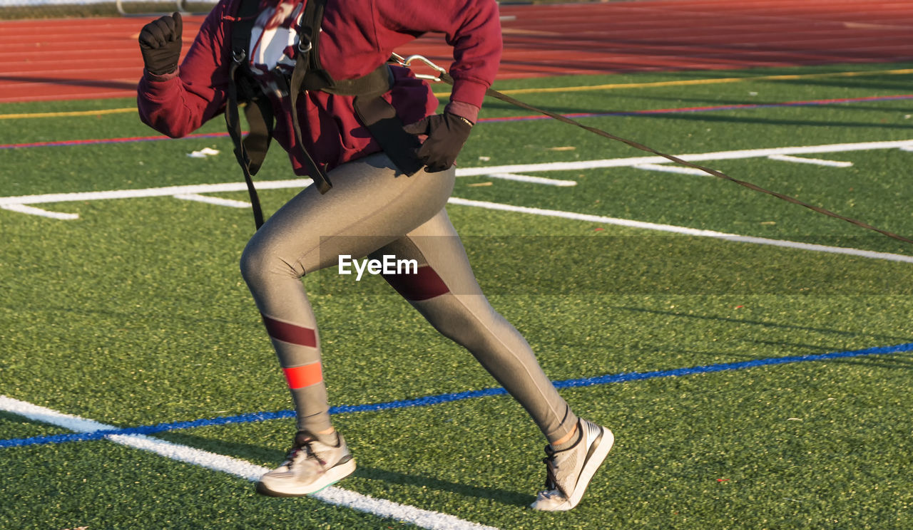 Low section of woman running on soccer field