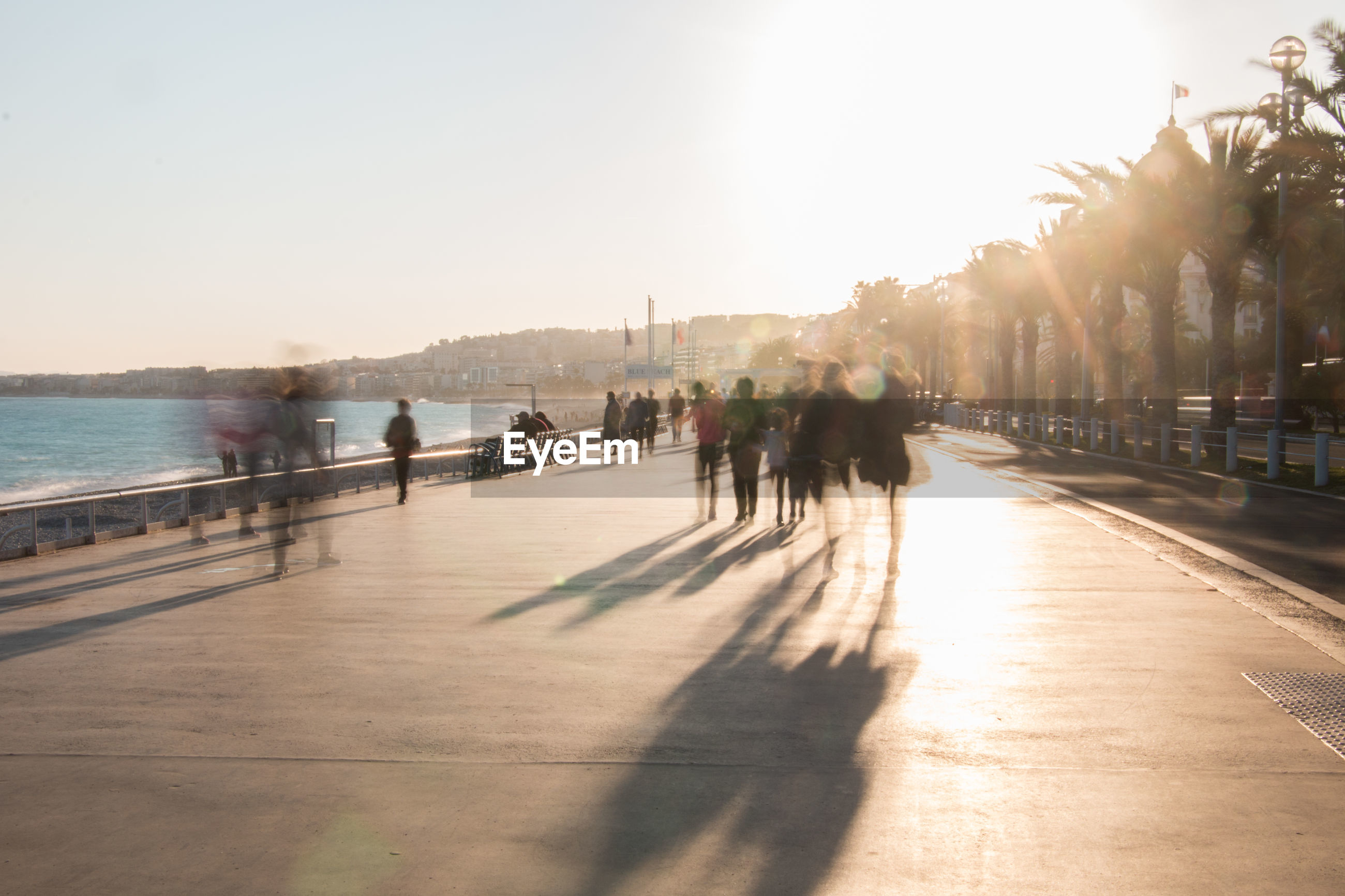 Blurred motion of people walking at promenade on sunny day