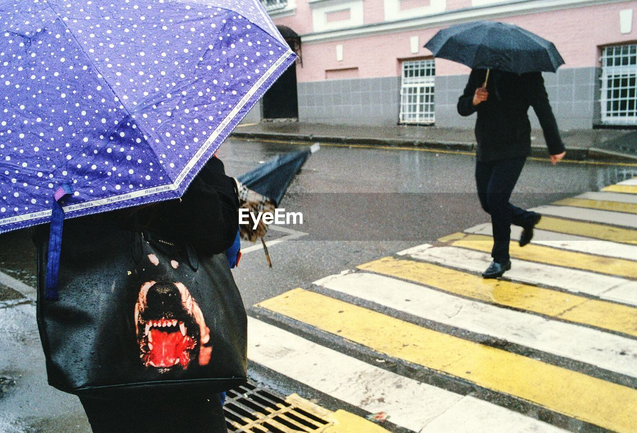 umbrella, city, rain, protection, transportation, walking, architecture, street, real people, men, wet, security, people, crosswalk, road marking, day, road, crossing, rainy season