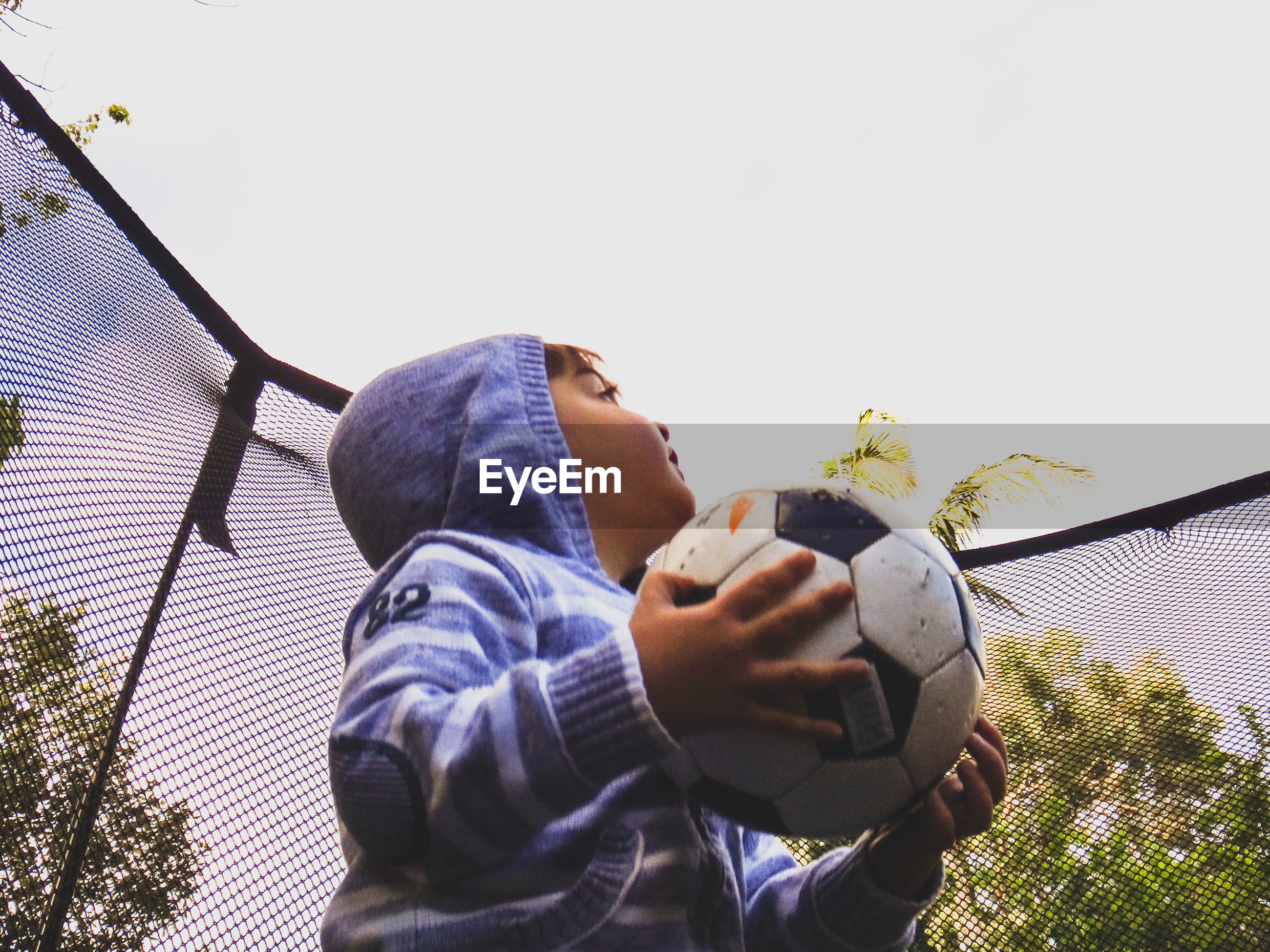 Low angle view boy looking up while holding soccer ball