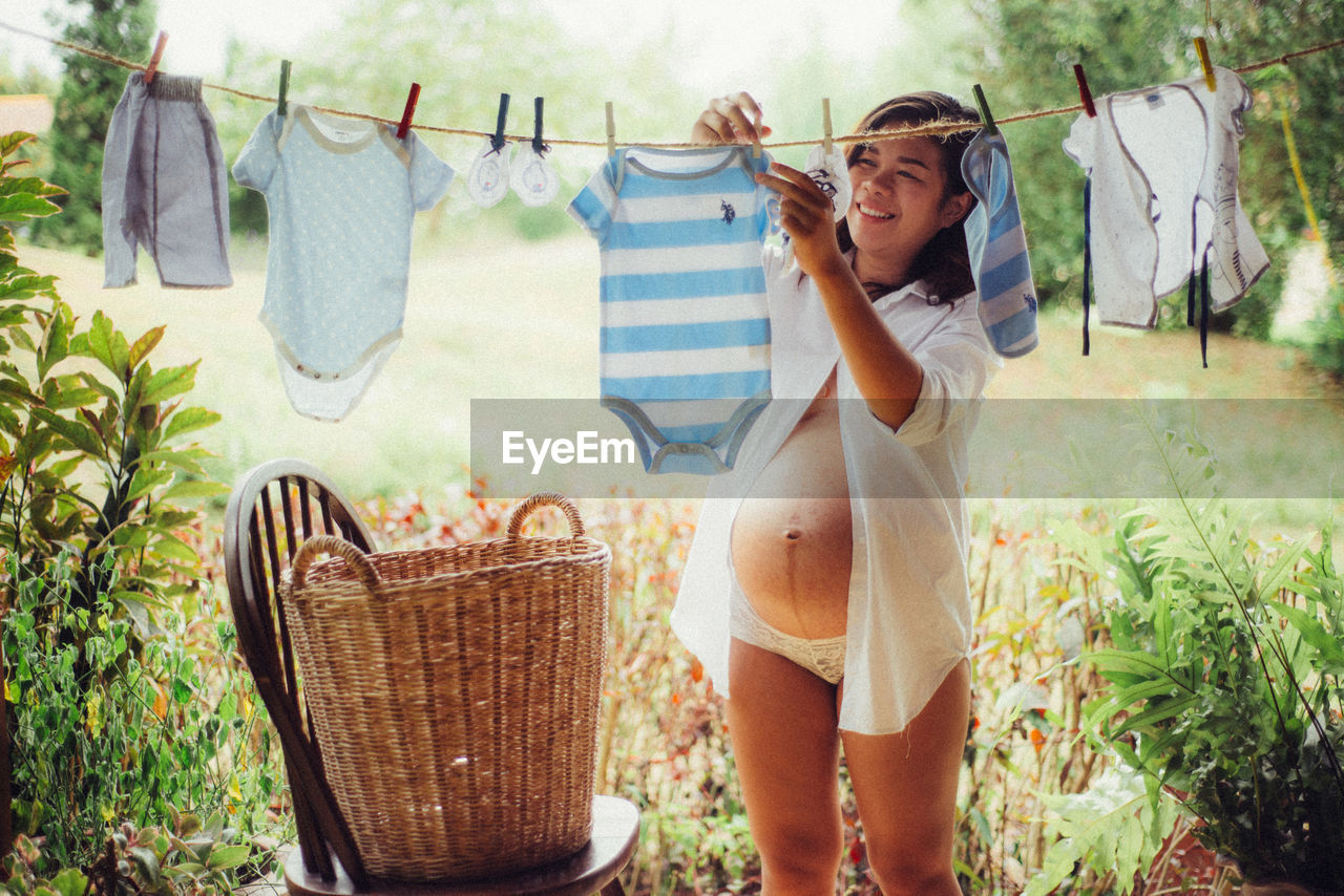 Pregnant Woman Hanging Baby Clothes On Clothesline