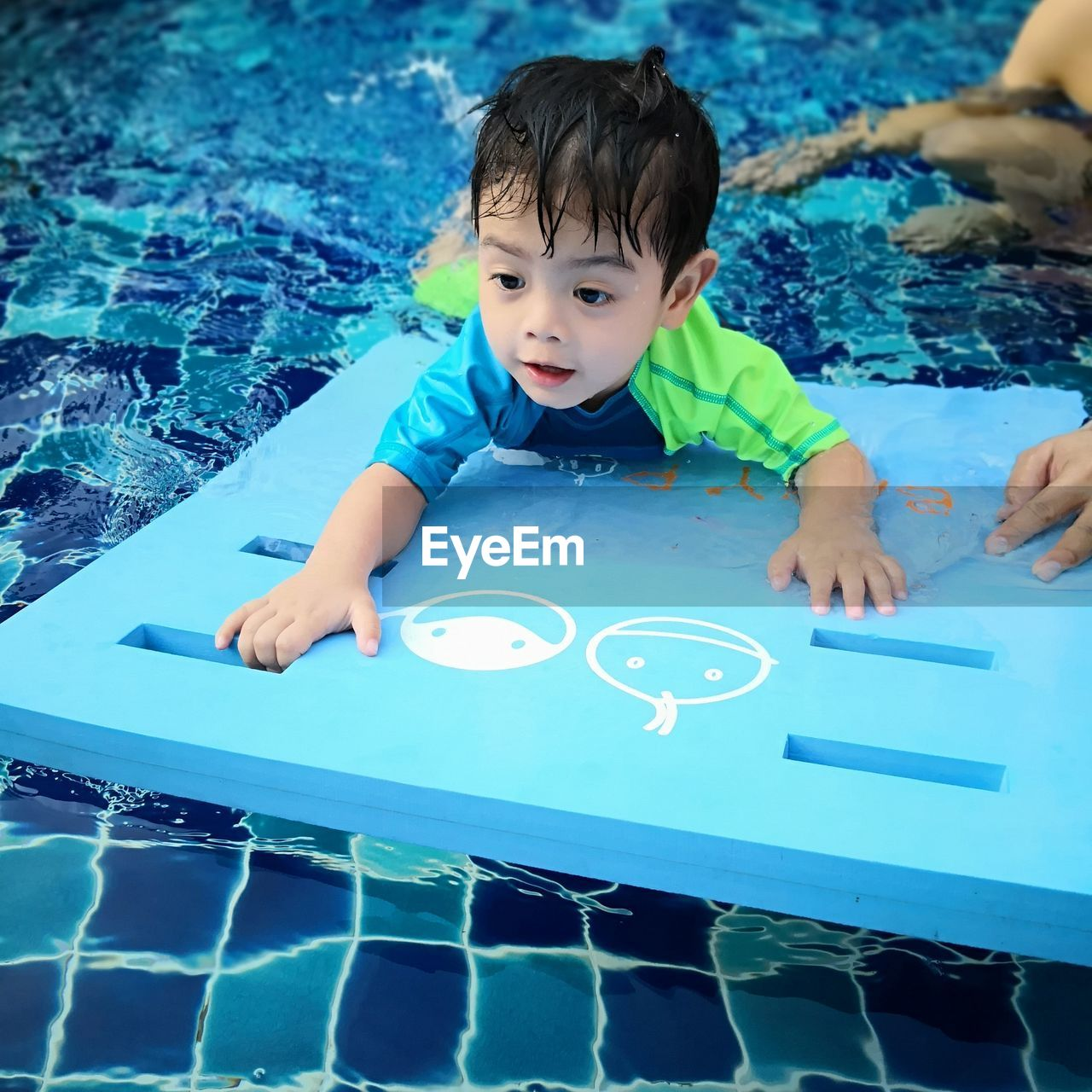 HIGH ANGLE PORTRAIT OF CUTE BOY FLOATING IN SWIMMING POOL