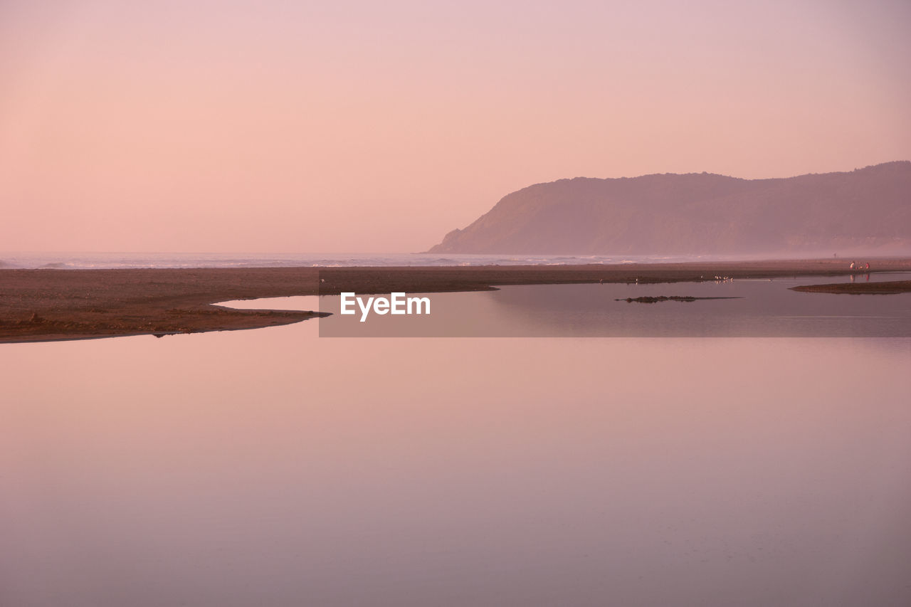 sky, water, tranquil scene, tranquility, beauty in nature, sunset, scenics - nature, mountain, non-urban scene, nature, idyllic, sea, copy space, reflection, no people, land, waterfront, beach, outdoors