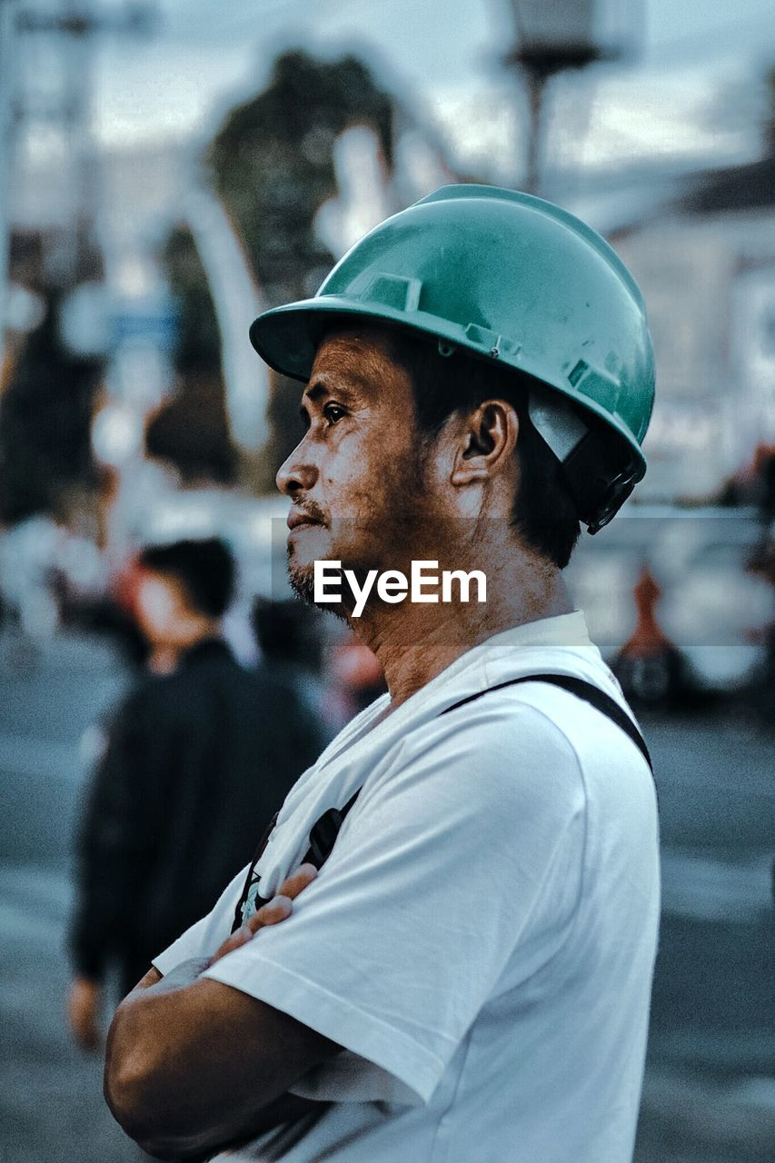 Profile view of male worker wearing green hardhat at construction site