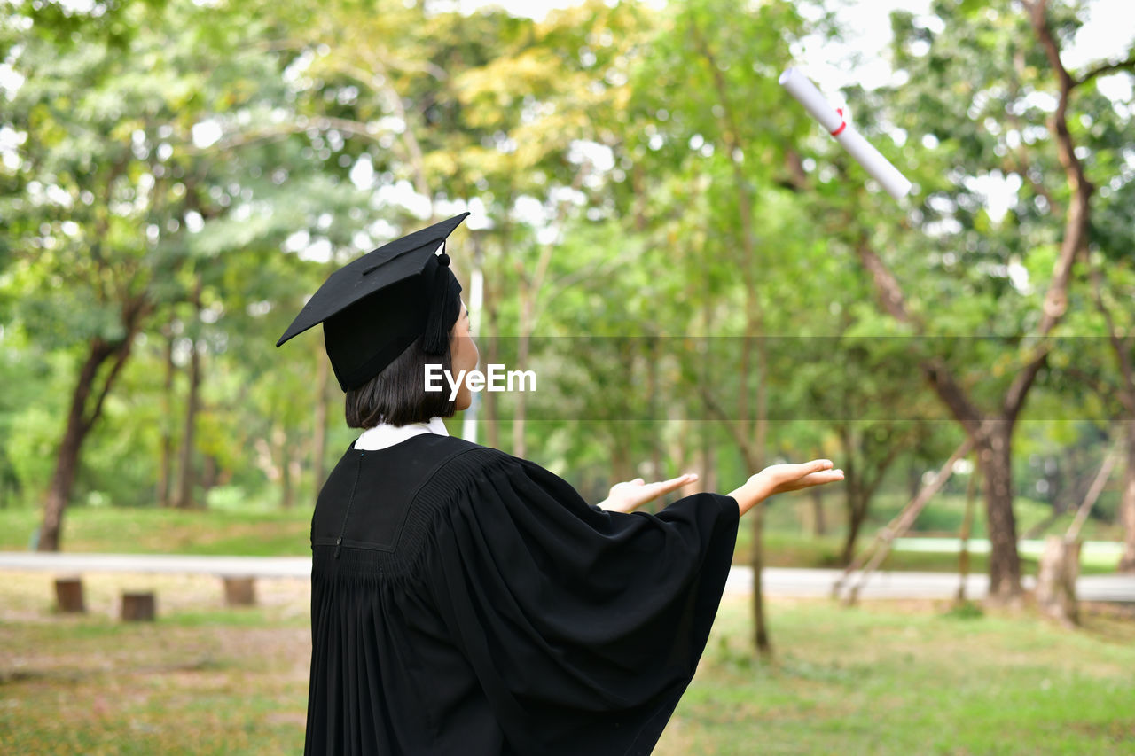 real people, one person, plant, day, focus on foreground, graduation, rear view, tree, mortarboard, standing, graduation gown, education, nature, waist up, land, adult, men, outdoors, achievement