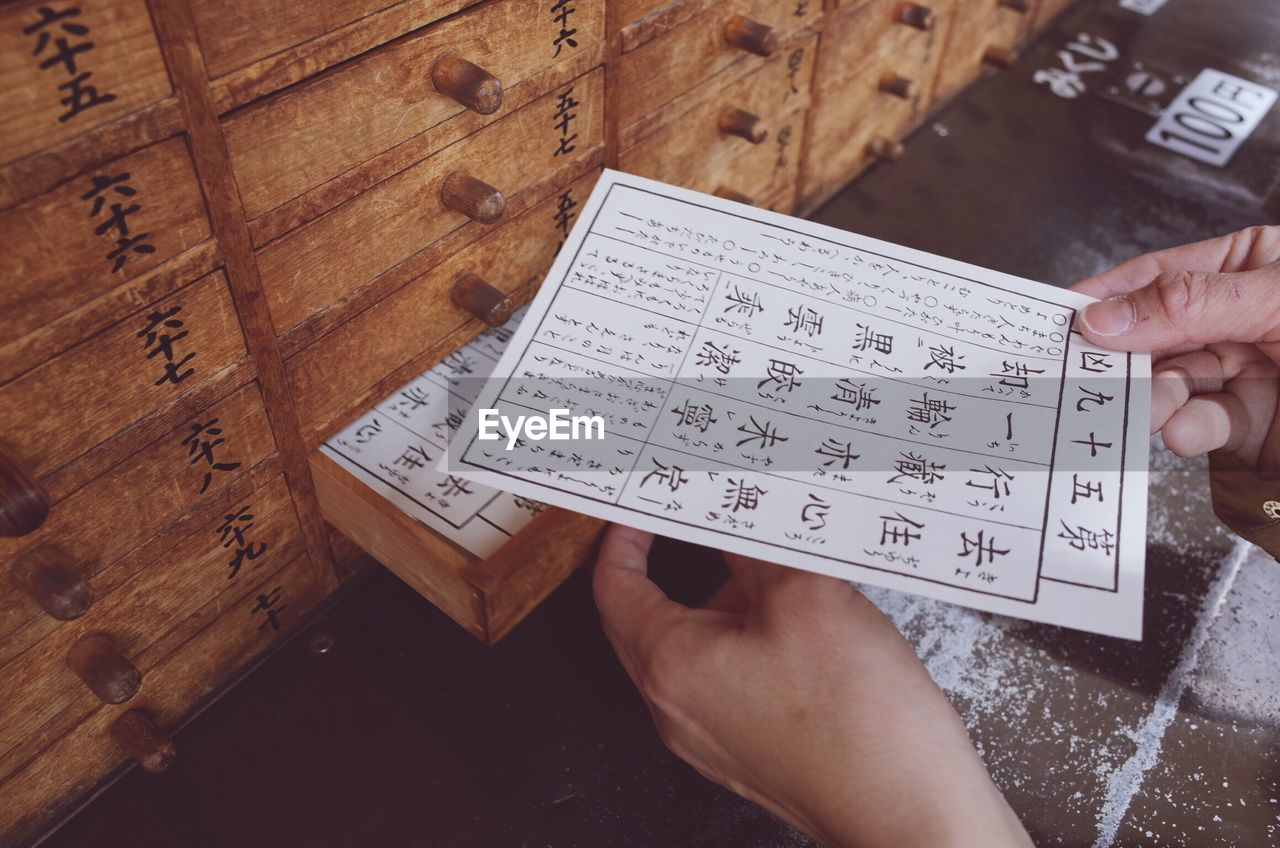 Cropped Image Of Person Holding Fortune Paper By Wooden Drawers