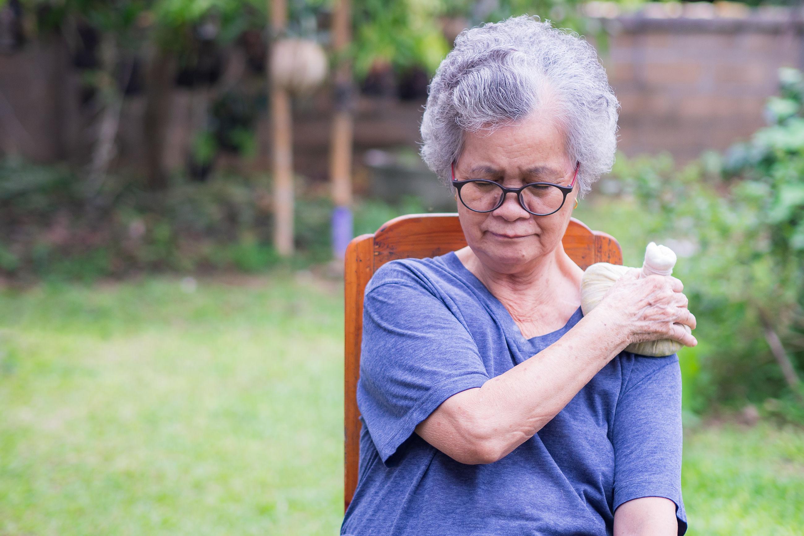 Elderly woman having shoulder pain use thai herbal compress ball on shoulder.