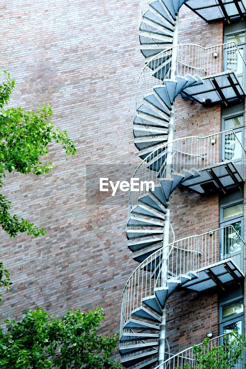 architecture, built structure, building exterior, day, wall, brick, no people, wall - building feature, brick wall, window, plant, building, low angle view, outdoors, pattern, staircase, steps and staircases, nature, residential district, fire escape, apartment