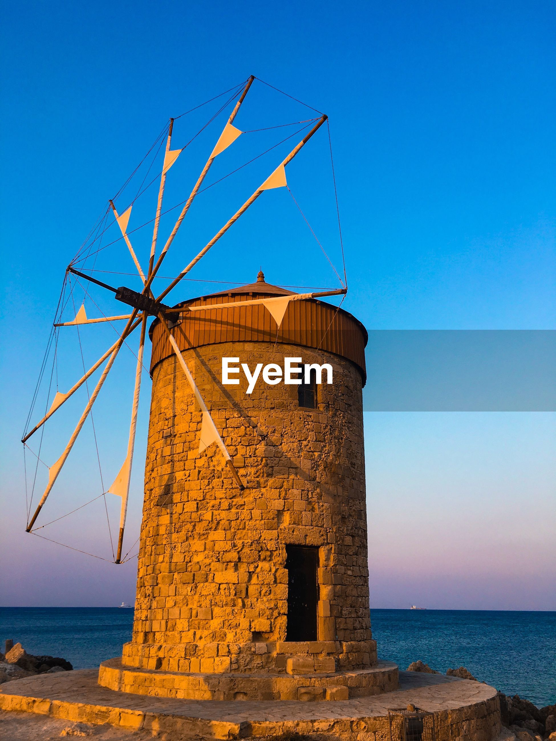 Traditional windmill by sea against clear blue sky
