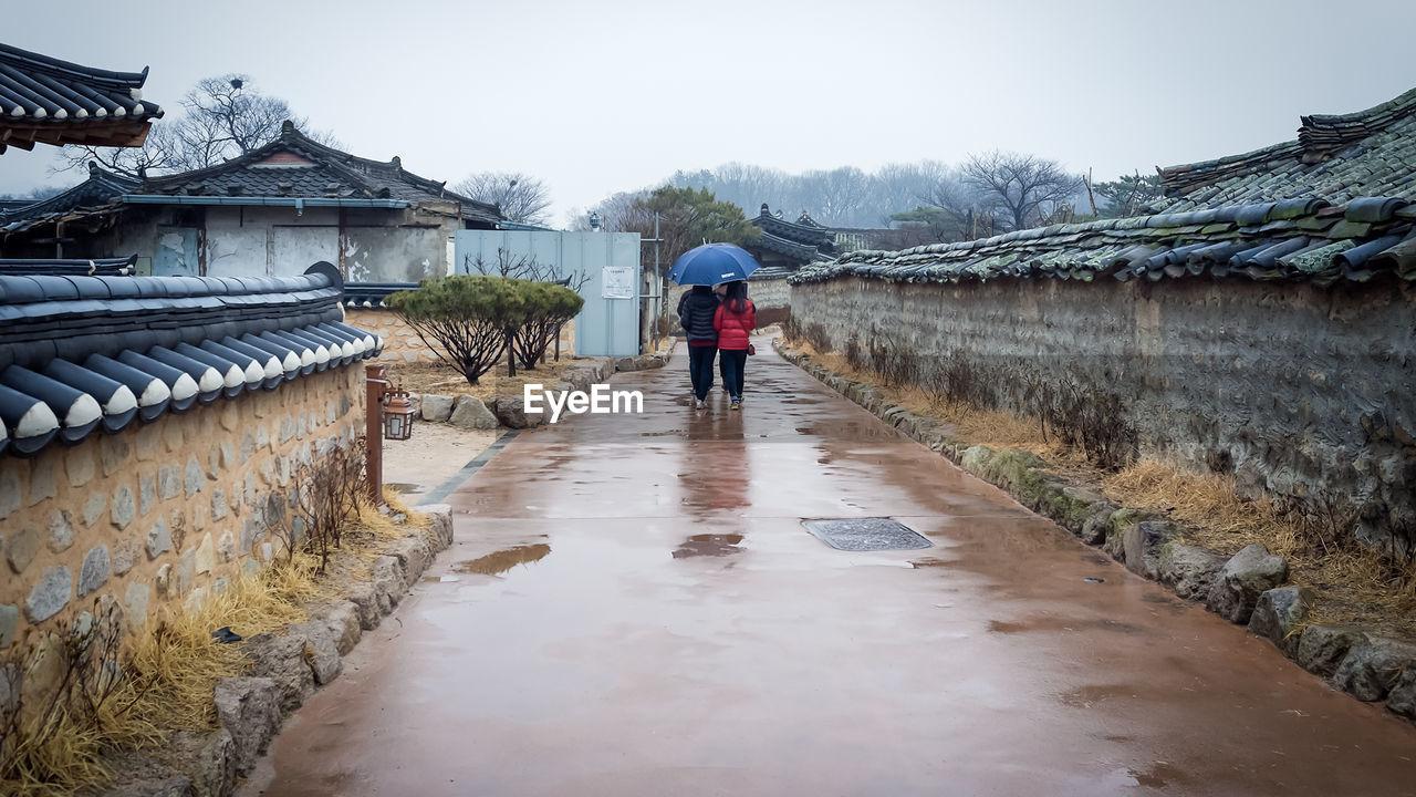 People Walking On Wet Street On Rainy Day Against Sky