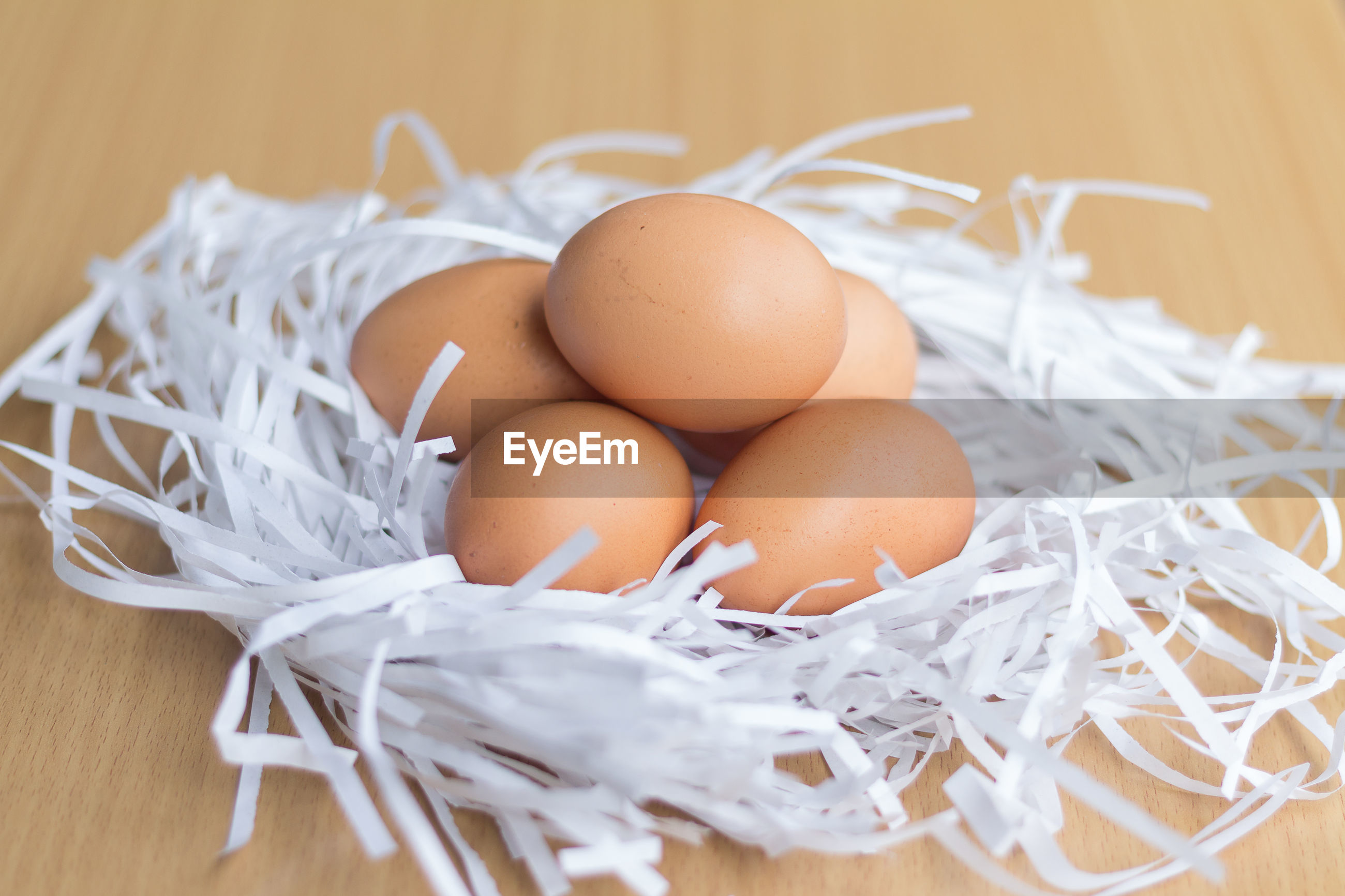 HIGH ANGLE VIEW OF EGGS IN CONTAINER ON FLOOR