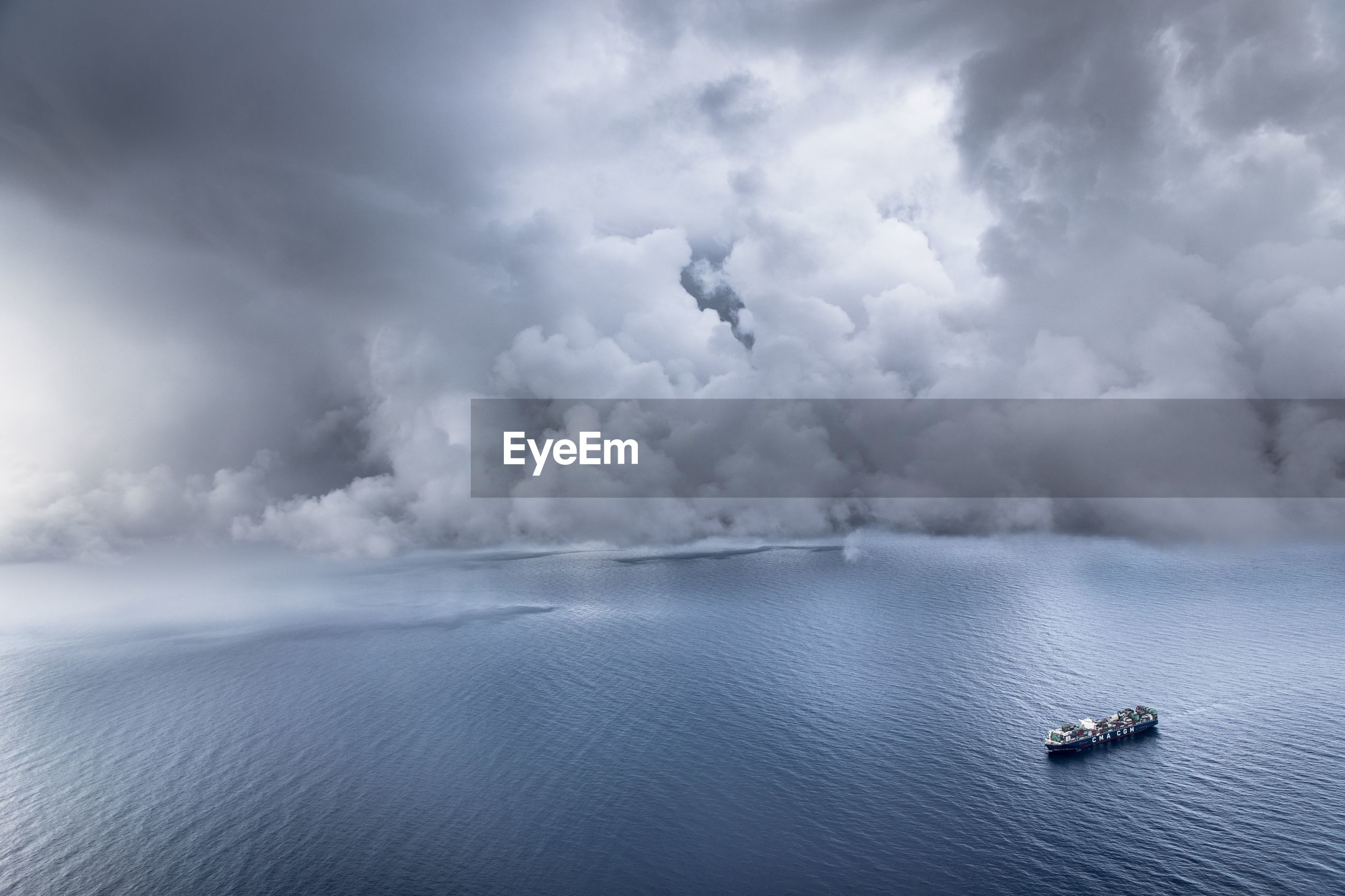Aerial view of boat on sea against cloudy sky