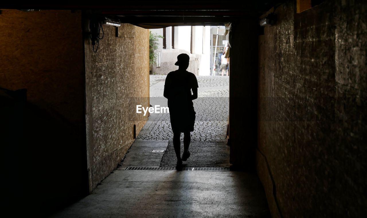 Rear View Of Boy Walking In Underground Tunnel