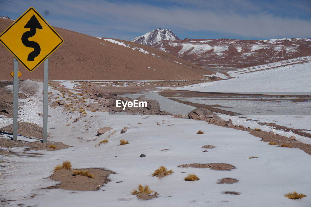 cold temperature, winter, snow, mountain, scenics - nature, sign, beauty in nature, no people, tranquility, nature, tranquil scene, sky, communication, non-urban scene, covering, road, yellow, day, snowcapped mountain