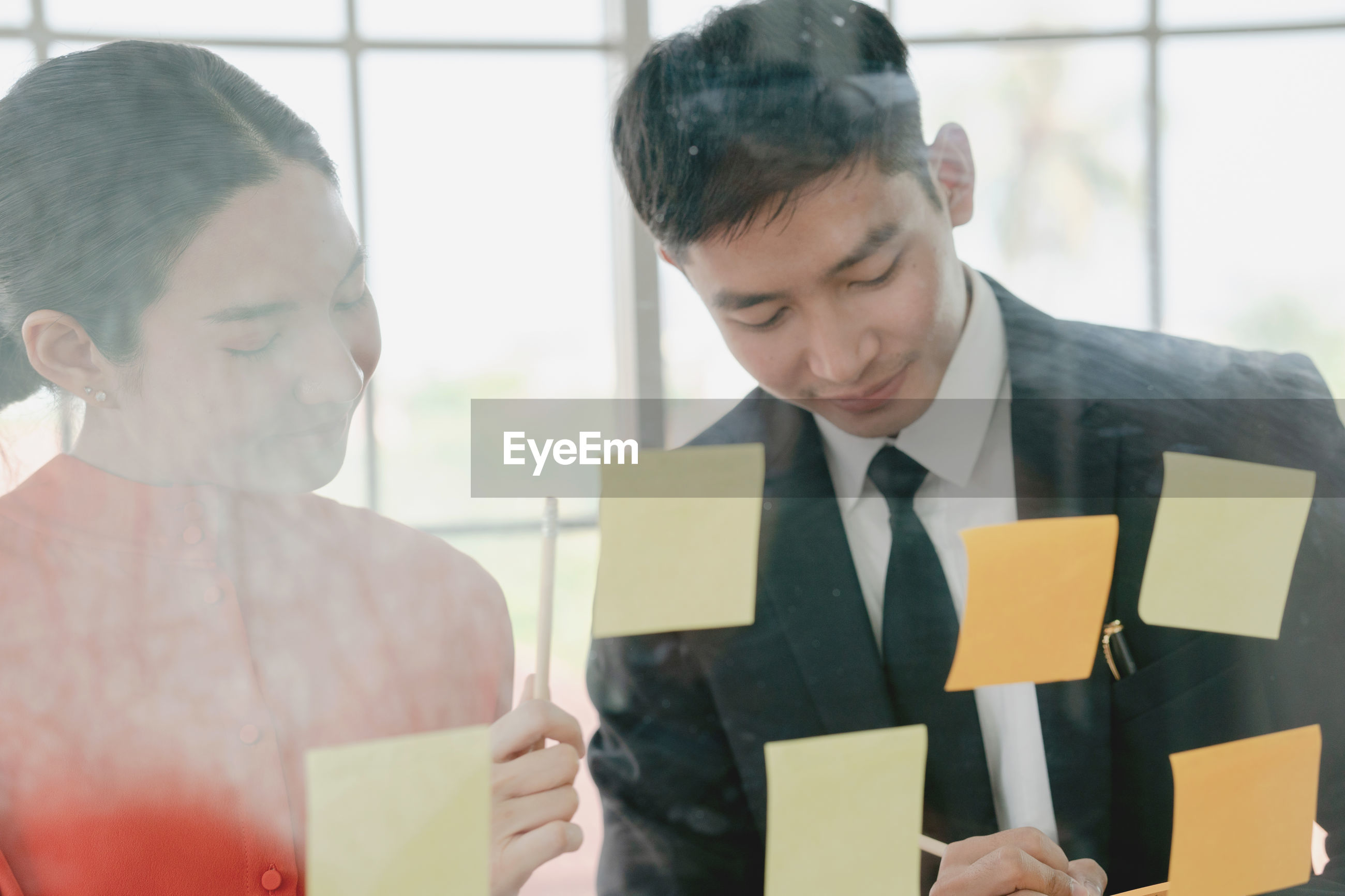 Smiling young man and woman by adhesive notes seen through glass window