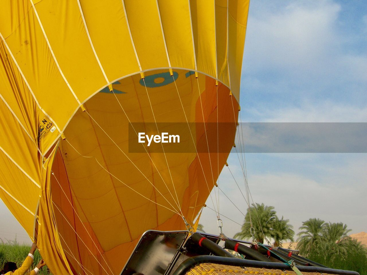 transportation, hot air balloon, balloon, sky, yellow, nature, air vehicle, adventure, day, mode of transportation, cloud - sky, low angle view, outdoors, extreme sports, no people, burning, fire, travel, inflating, flame