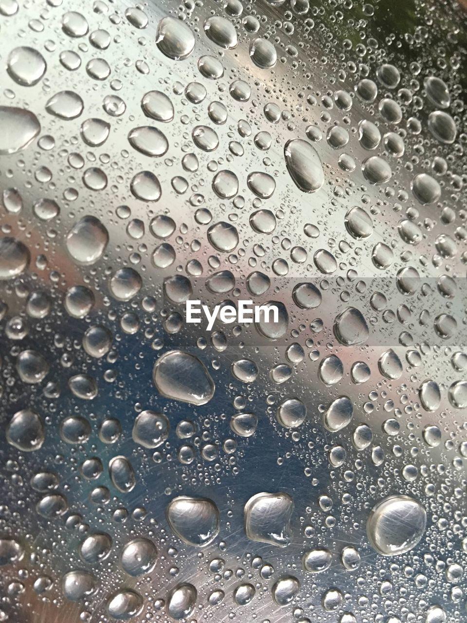 Full frame shot of glass with raindrops
