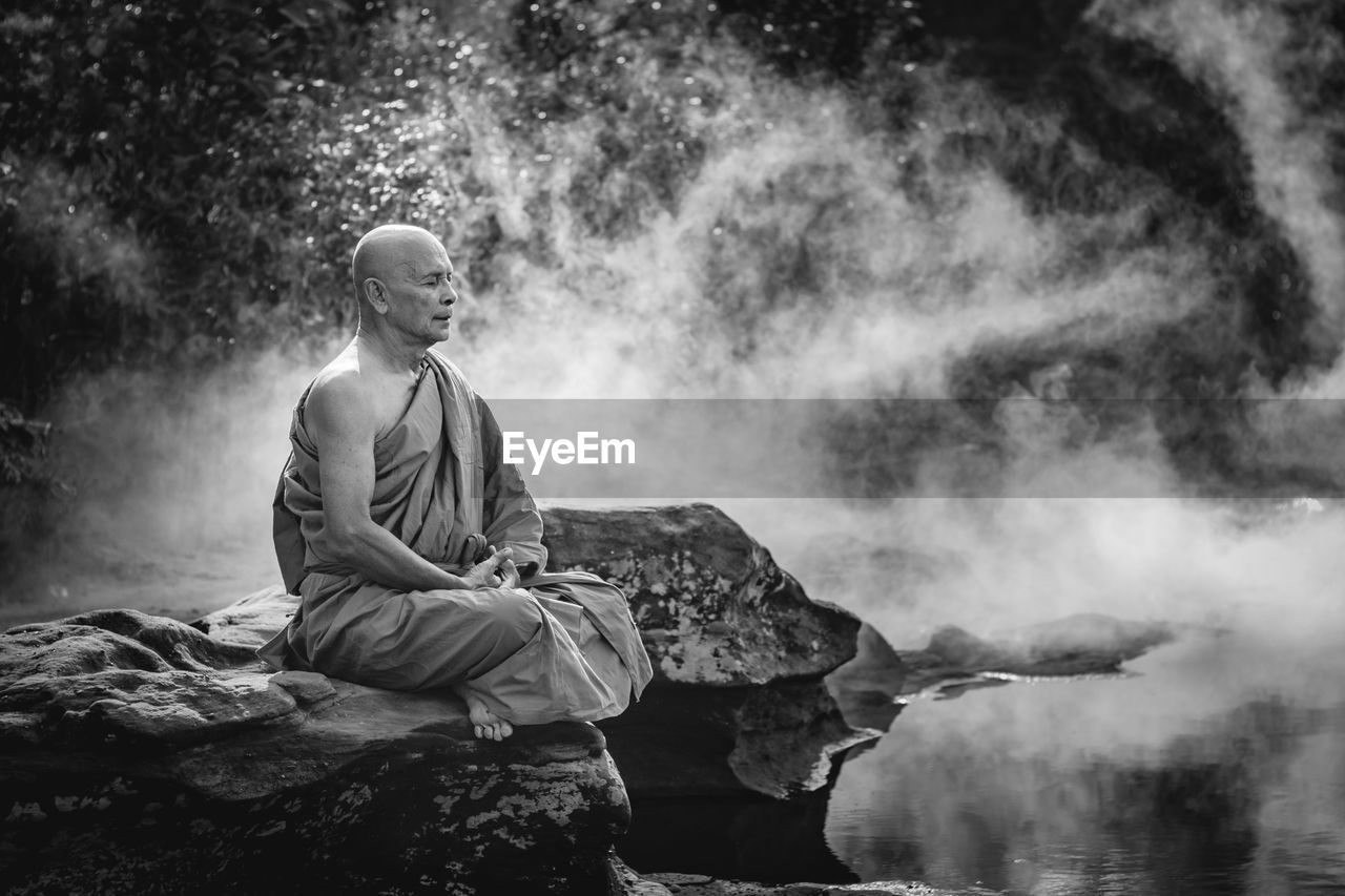 Full length of monk meditating while sitting on rock by river