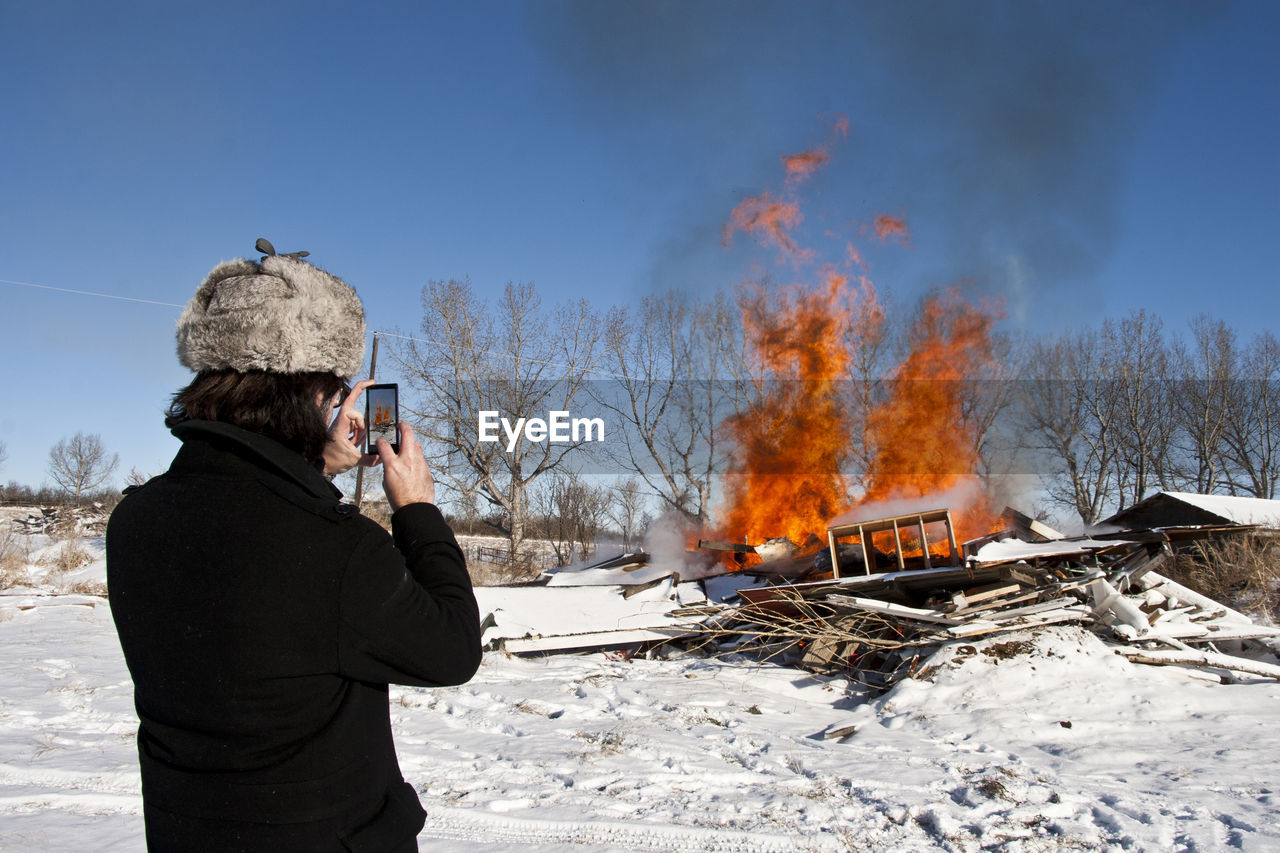 Rear View Of Woman Photographing Fire On Snow Covered Field