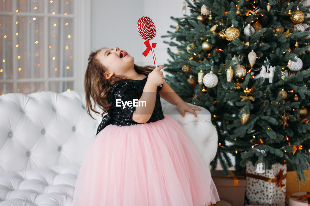 Happy girl with candy standing against christmas tree