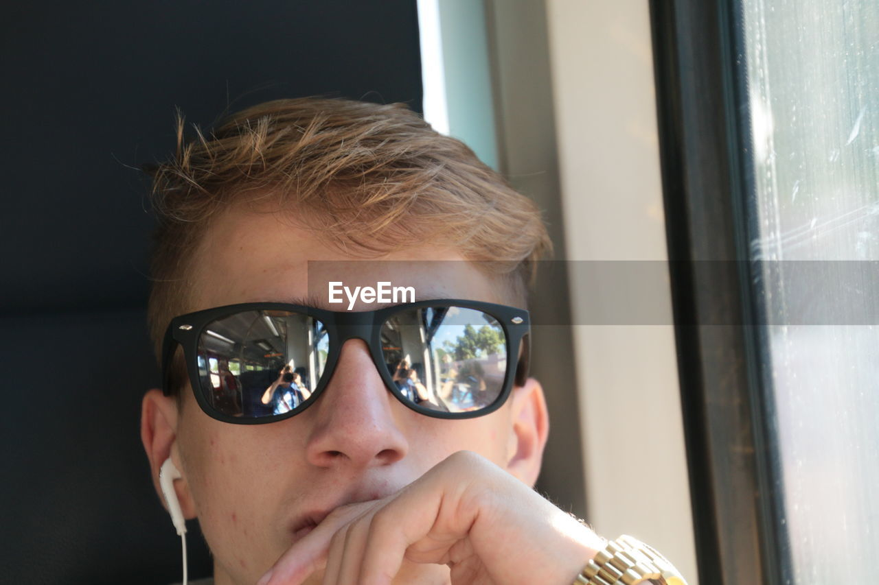 Close-up of man wearing sunglasses with reflection of friend photographing while traveling in train