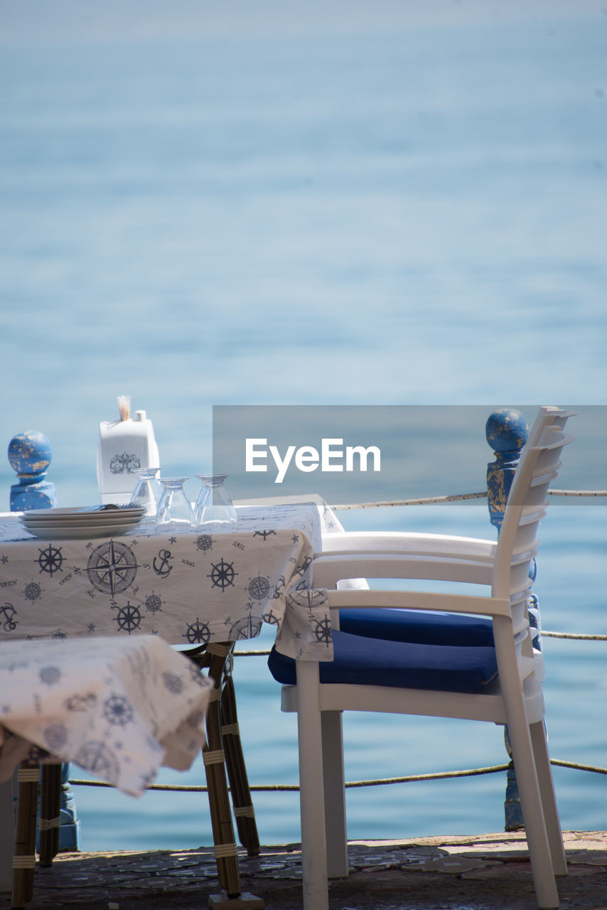 water, sea, day, nature, no people, beach, sky, land, beauty in nature, focus on foreground, scenics - nature, outdoors, tranquil scene, tranquility, travel destinations, chair, non-urban scene, wood - material, tourism