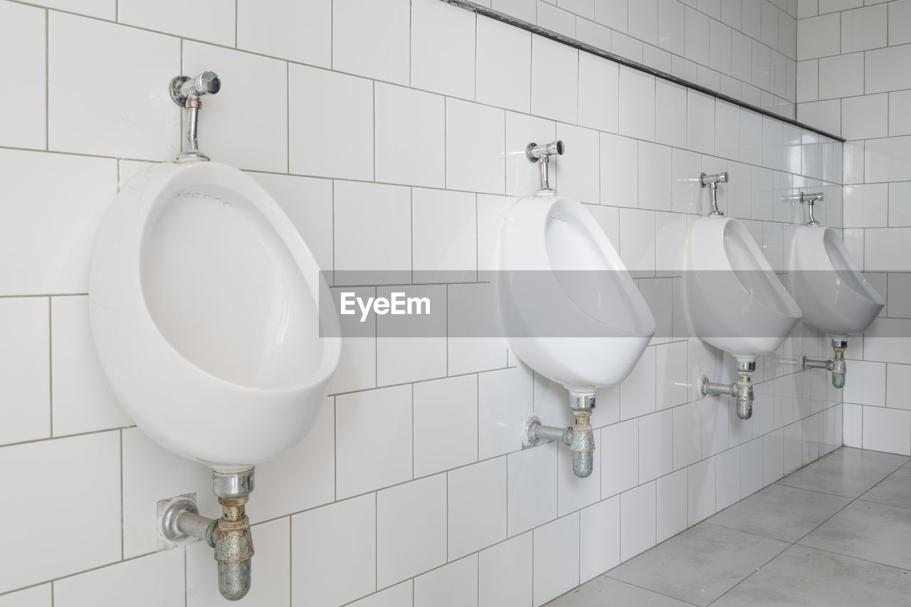 tile, bathroom, flooring, indoors, hygiene, toilet, wall - building feature, domestic room, no people, public building, public restroom, white color, urinal, domestic bathroom, in a row, clean, tiled floor, home, convenience, white