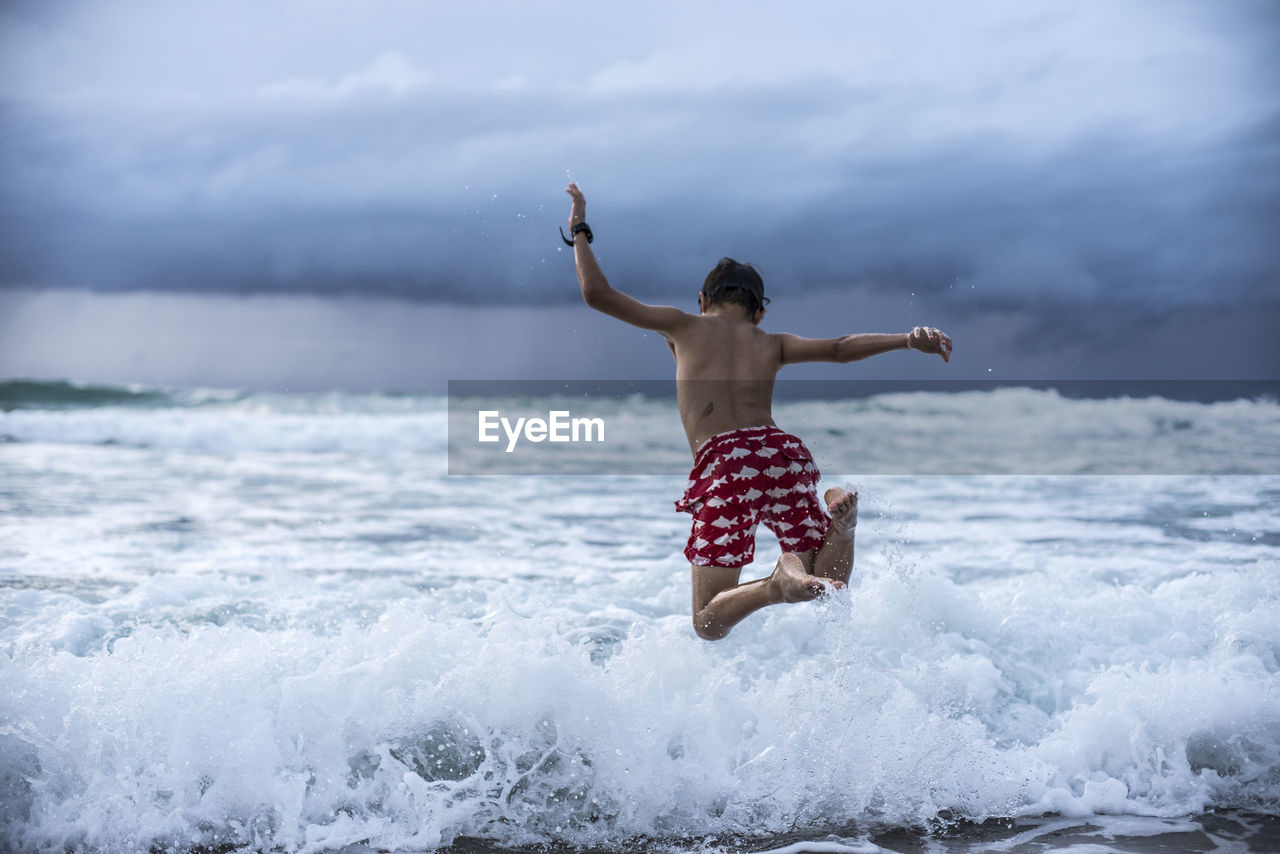 Rear View Of Shirtless Boy Jumping In Sea Against Cloudy Sky