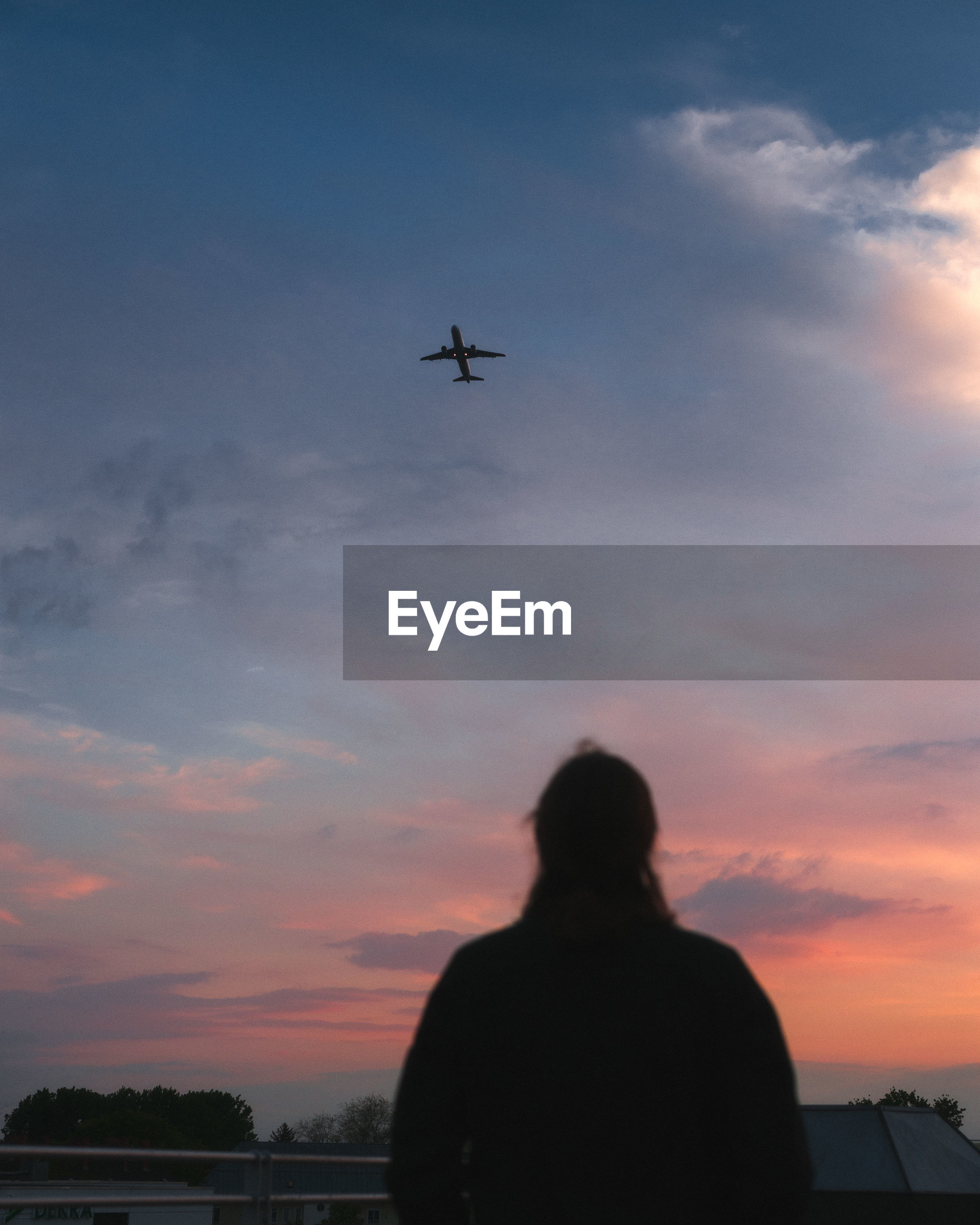 Low angle view of silhouette airplane and woman against sky during sunset