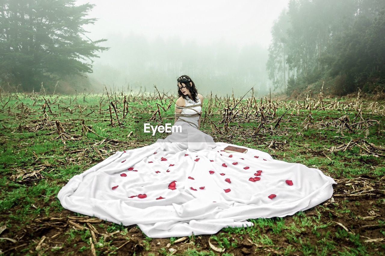 Woman wearing white dress while wrapped in rope on field