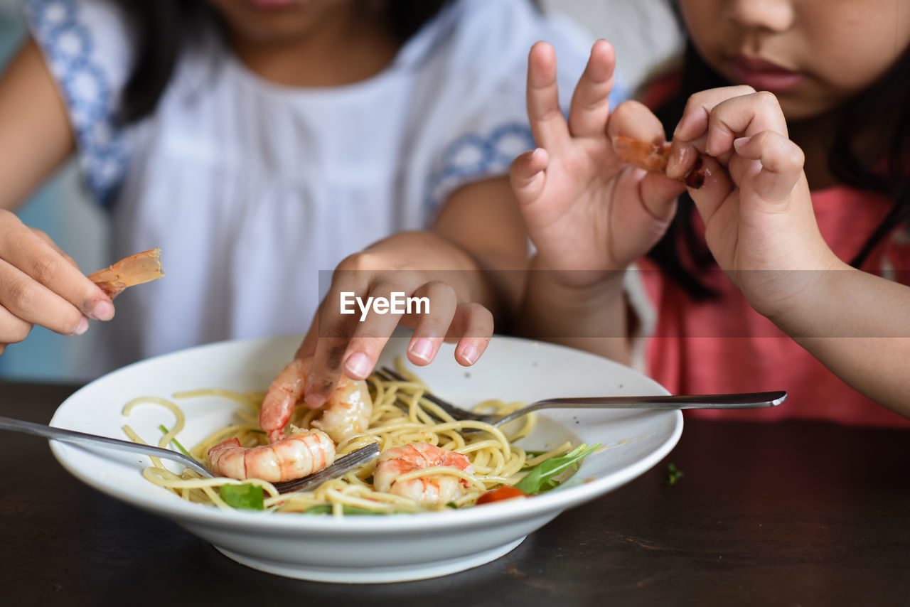 Close-Up Of Sisters Eating Prawn Noodles In Plate At Table