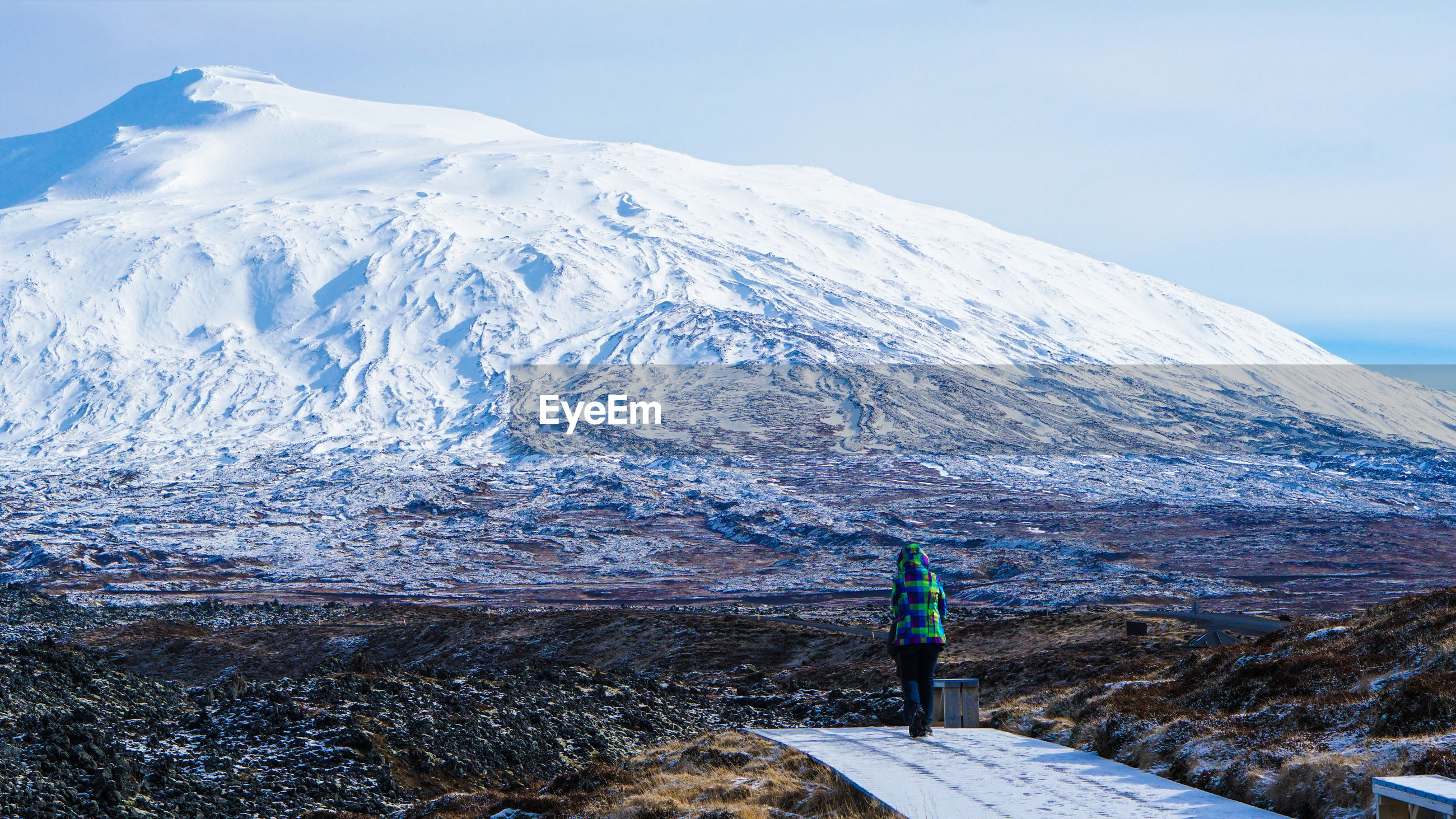 Rear view of woman against snowcapped mountain
