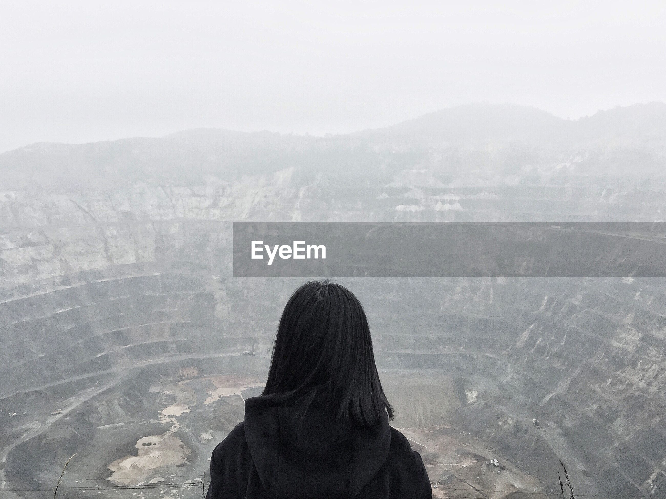 Rear view of woman standing against open-pit mine during foggy weather