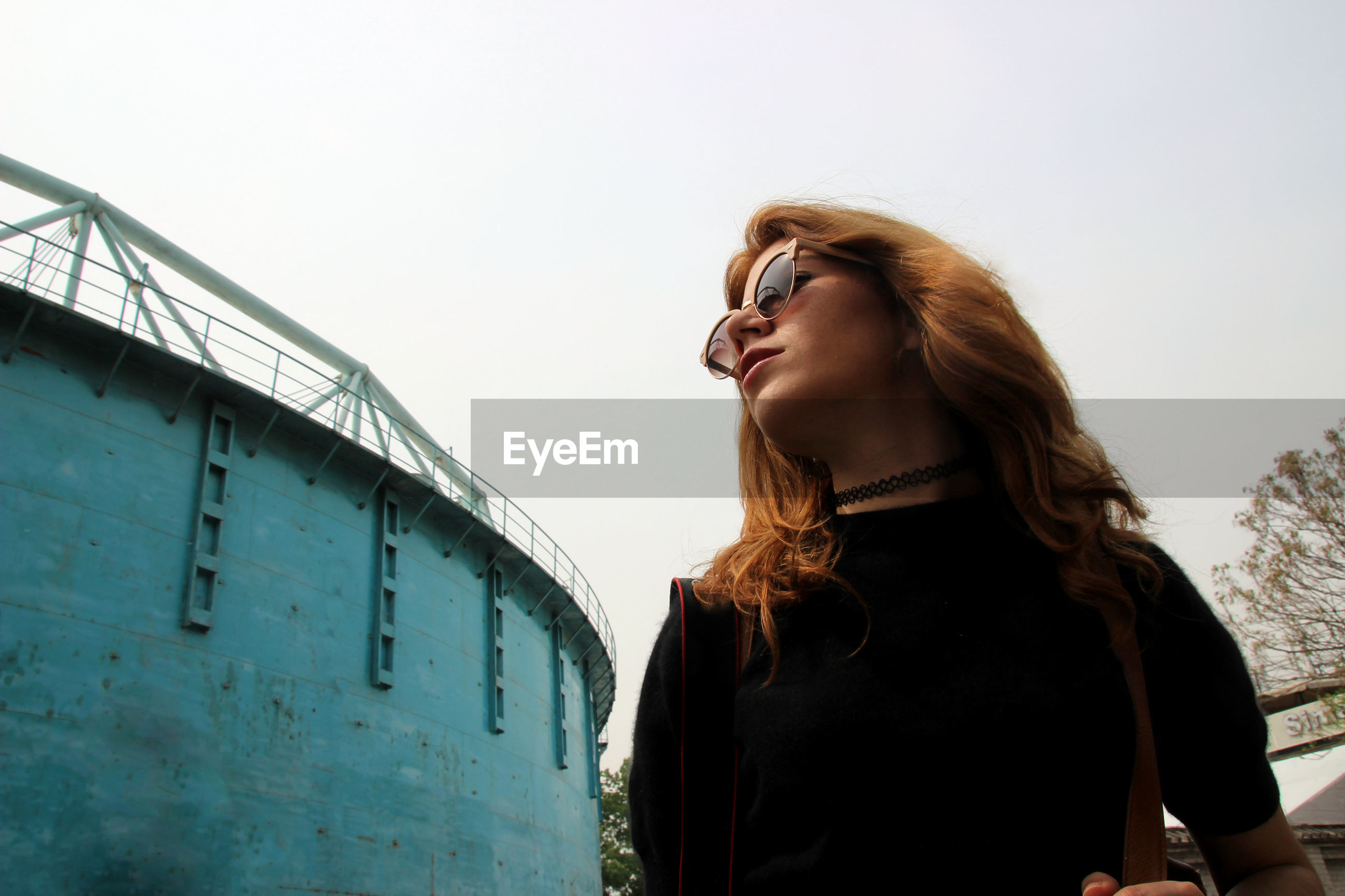Low angle view of young woman wearing sunglasses standing against clear sky
