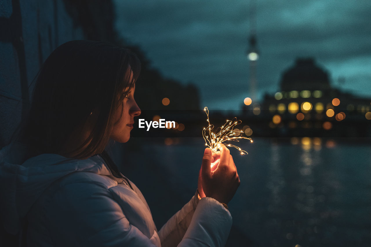 illuminated, focus on foreground, leisure activity, real people, women, one person, lifestyles, holding, glowing, young women, water, nature, night, young adult, standing, firework, burning, architecture, sparkler, firework - man made object, hairstyle, outdoors, sparks