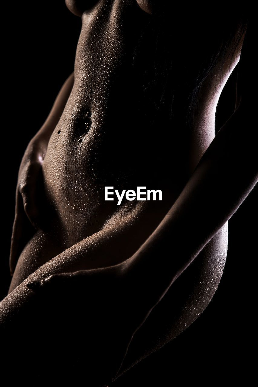 one person, black background, indoors, close-up, human skin, skin, human body part, midsection, studio shot, lifestyles, body part, real people, shirtless, adult, front view, dark, women, human face, human body, beautiful woman