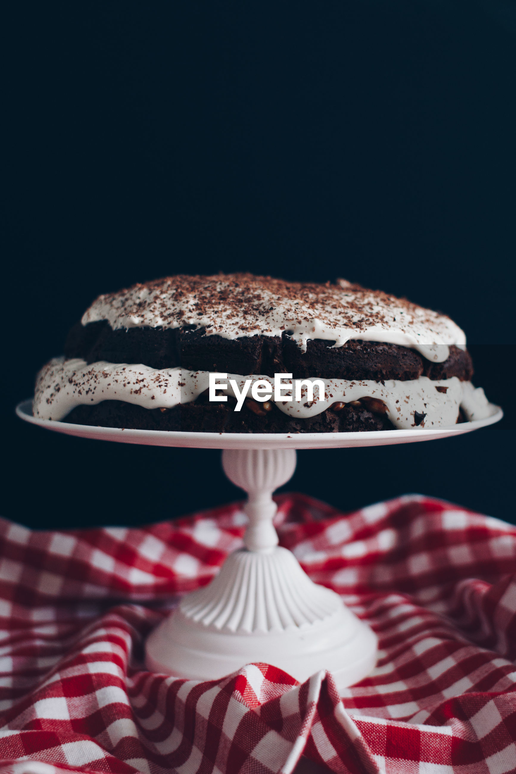 Cake on stand against black background