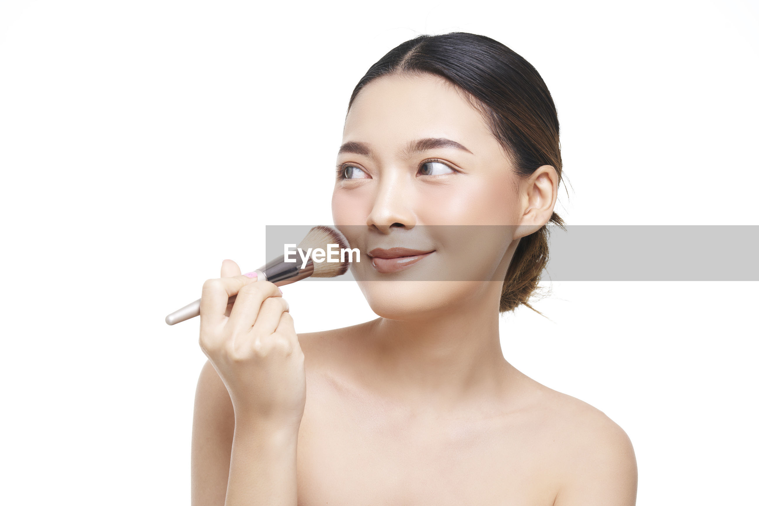 Close-up of smiling young woman applying make-up against white background