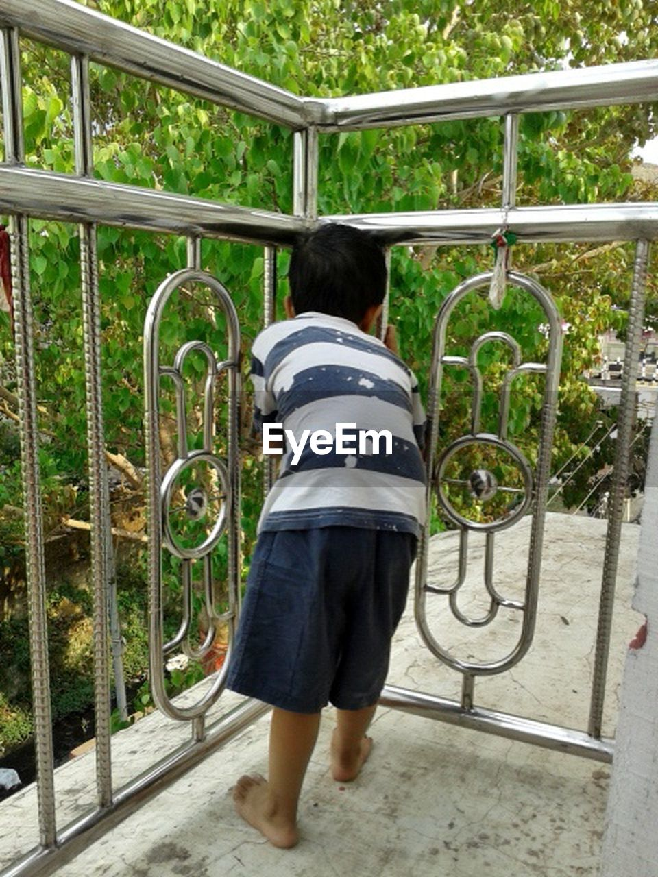 one person, rear view, full length, day, standing, childhood, leisure activity, real people, casual clothing, architecture, child, railing, playground, plant, staircase, metal, lifestyles, outdoors, striped, jungle gym, outdoor play equipment, hairstyle