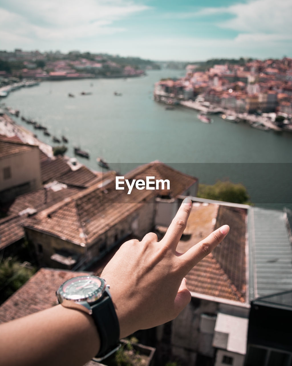 Cropped hand of person gesturing over houses and sea