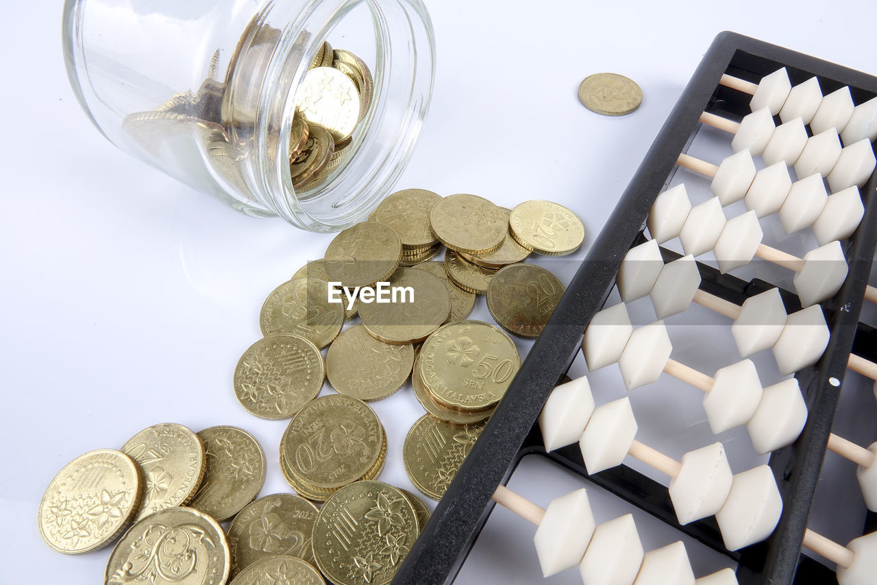 Close-up of abacus and golden coins over white background