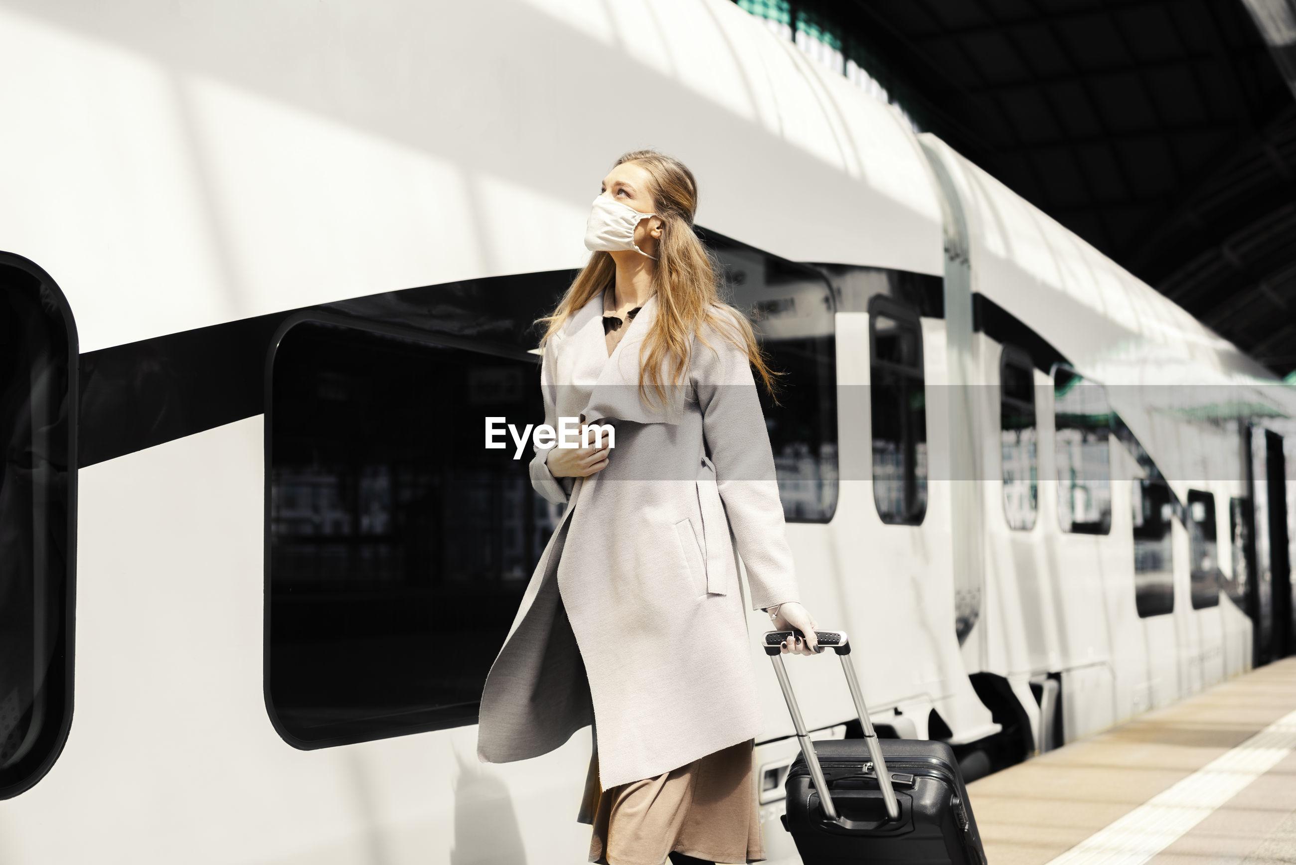 Woman wearing mask walking at railroad station