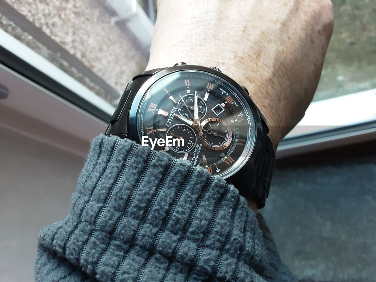 HIGH ANGLE VIEW OF HAND HOLDING CLOCK AGAINST BLURRED BACKGROUND