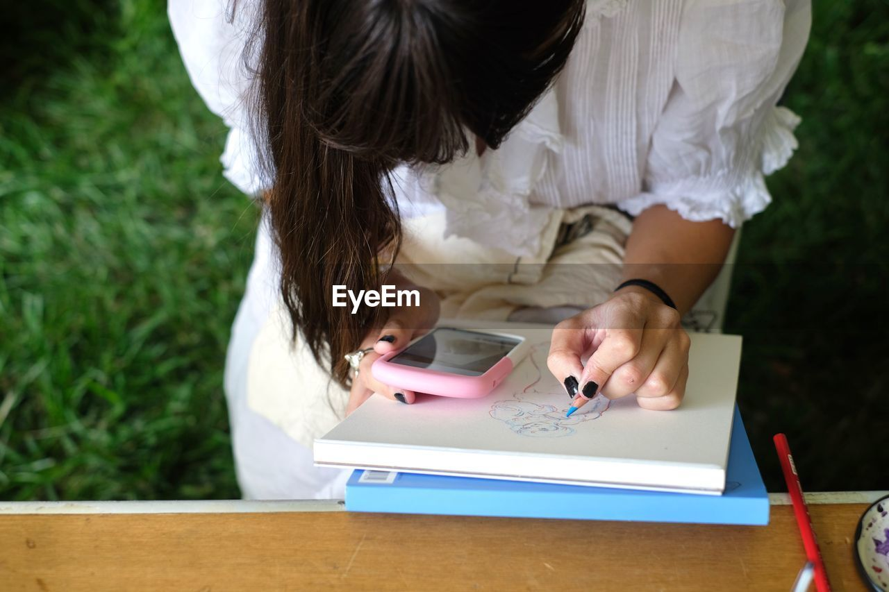 High Angle View Of Woman Using Mobile Phone While Drawing On Paper Over Field