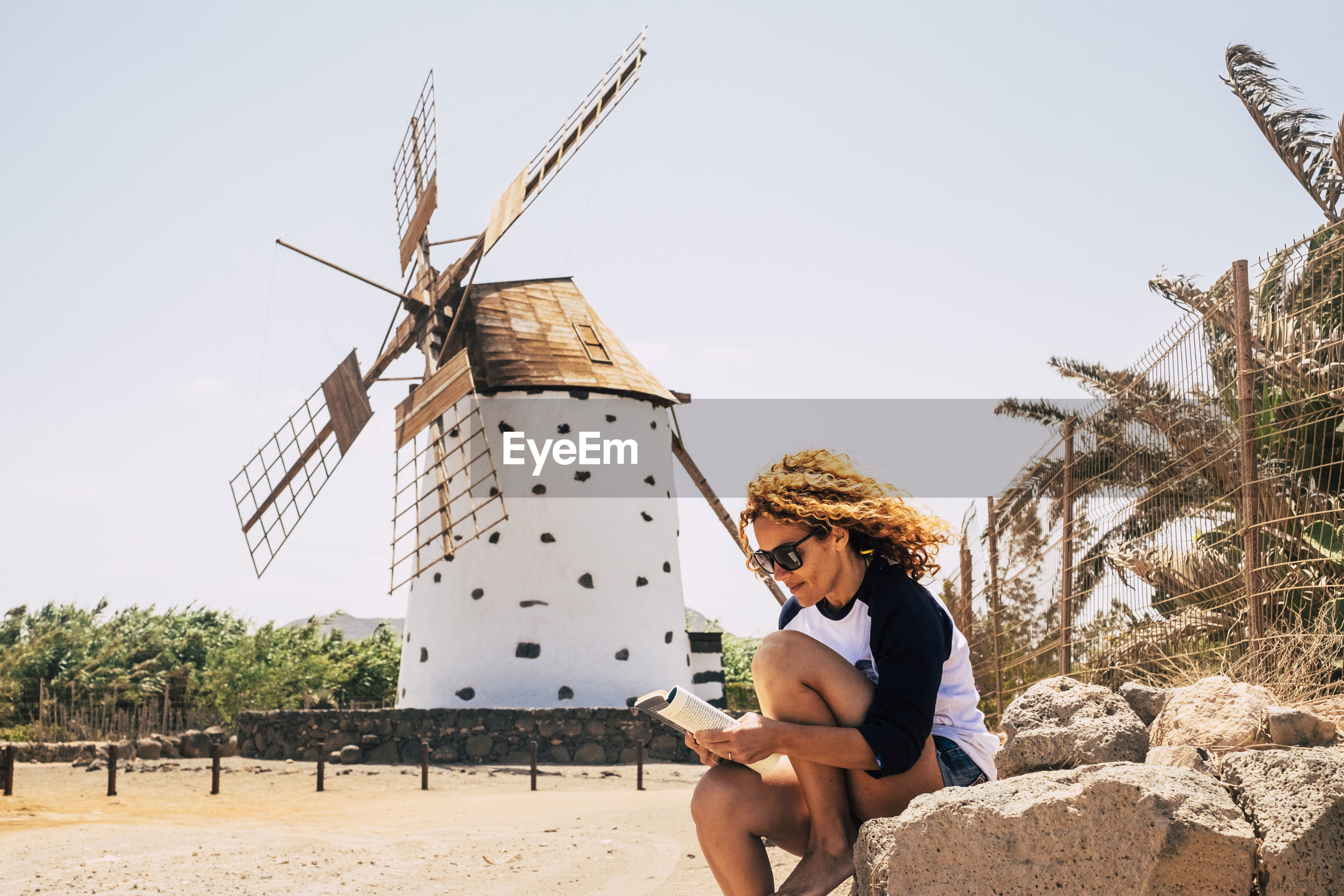 Woman reading book while sitting on rock by traditional windmill against sky