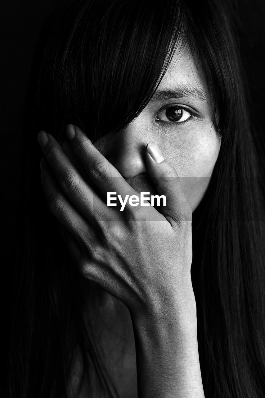 portrait, one person, headshot, human hand, real people, hand, lifestyles, close-up, front view, hair, indoors, hairstyle, looking at camera, leisure activity, black hair, human body part, obscured face, young adult, body part, human face, human hair, black background, finger, bangs